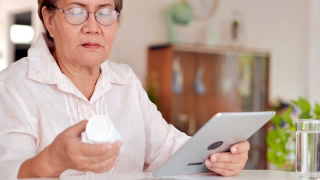 asian older women patient having video chat with doctor about how to take pills on tablet computer at home.technology,healthcare, innovation, well-being, care, strength, fitness and vitality,medical,education,retirement,healthcare and medicine - medicare stock videos & royalty-free footage