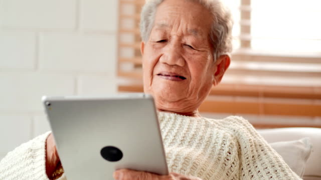 asian older women patient having video conference with doctor on tablet pc at home.senior holidays,technology, people, retirement, lifestyle, global, medical education, medical consultation, healthcare and medicine concept.senior technology - concept stock videos & royalty-free footage
