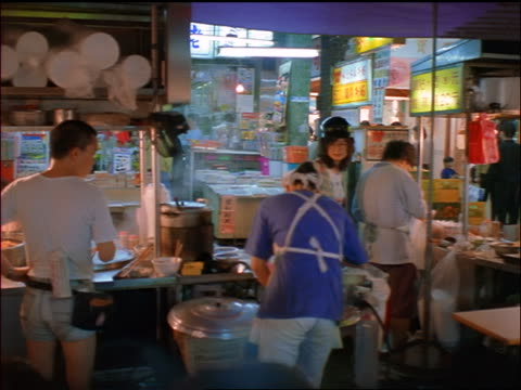 rear view pan-asian outdoor vendors preparing food under awning / night market, taipei, taiwan - asian market stock videos and b-roll footage