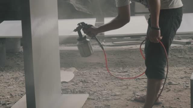 vidéos et rushes de peintre asiatique dans une usine. peinture industrielle avec pistolet - vidéo de stock - pression physique