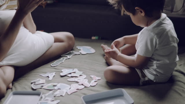 asian parent and child playing with jigsaw puzzle. - puzzle stock videos & royalty-free footage