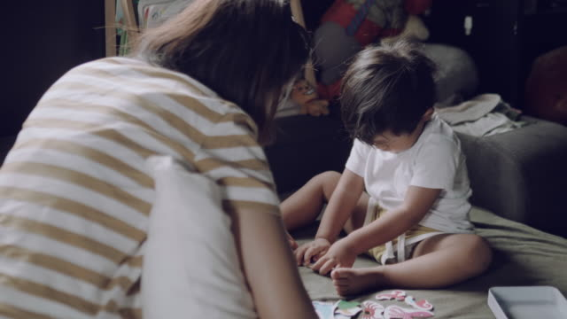asian parent and child playing with jigsaw puzzle. - 18 23 months stock videos and b-roll footage