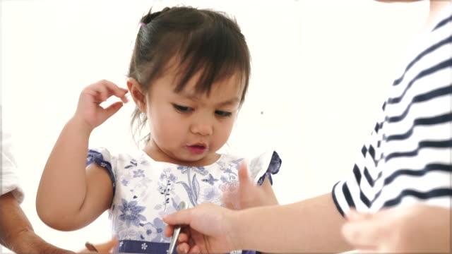 vídeos y material grabado en eventos de stock de padre asia alimentación de su hija y el hijo-acción video - comida de bebé