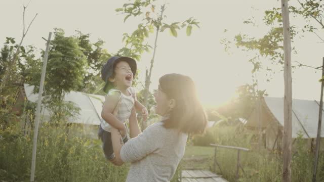 秋の森の赤ちゃんを持ち上げるアジアの親 - テント点の映像素材/bロール
