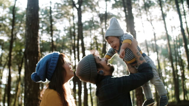 Asian parents lifting baby in forest in autumn