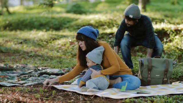 キャンプ旅行に男の子の赤ちゃんを持つアジアの親 - テント点の映像素材/bロール
