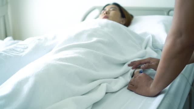 asiatiska patienten sjuk i sängen innehav hand familjer - mar bildbanksvideor och videomaterial från bakom kulisserna