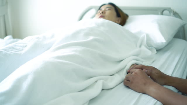 asian patient ill in bed holding hand families - mar stock videos & royalty-free footage