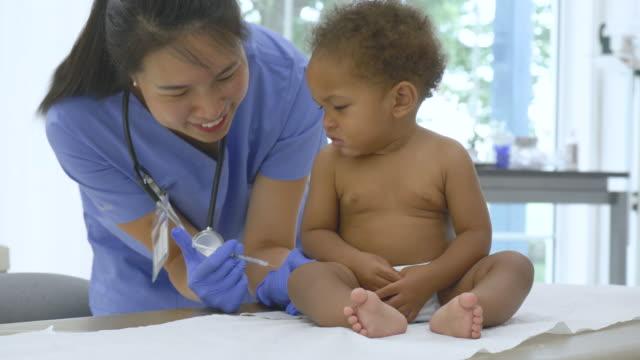 vídeos de stock e filmes b-roll de asian pediatrician giving a baby a vaccination - vacina