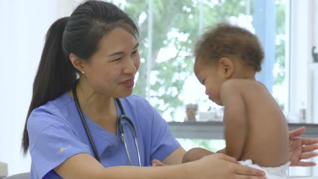 vídeos de stock, filmes e b-roll de o pediatra asiático executa a verificação médica no bebê - baby boys