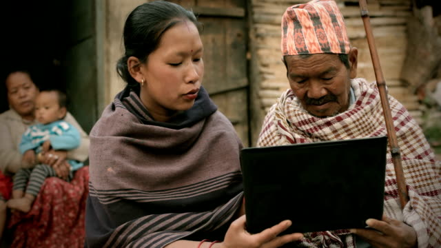 asian people: a young woman showing laptop to senior man - rural scene stock videos & royalty-free footage
