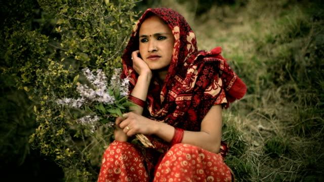 vidéos et rushes de asian personnes: belle femme assise dans la nature avec des fleurs. - cadrage aux genoux