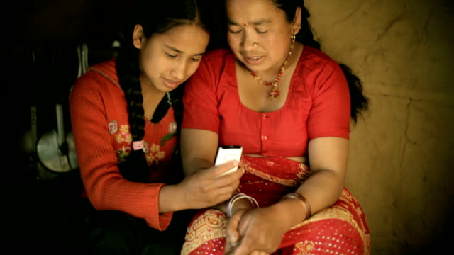 Asian people: Daughter showing mobile phone to her mother