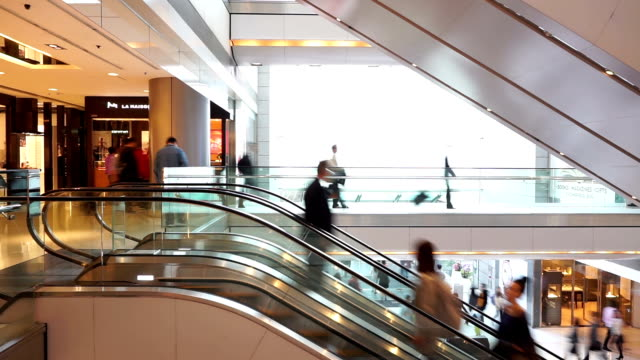 Asian people on shopping mall escalator, time lapse.