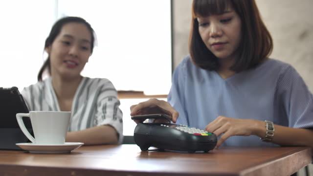 アジア人、非接触型決済、カフェで携帯電話でお支払い - 支払い点の映像素材/bロール