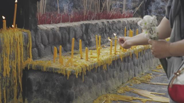 Asian people praying buddha, joss stick and candle flame.