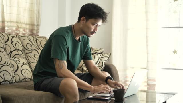 vídeos y material grabado en eventos de stock de los asiáticos se sientan y usan computadoras portátiles en el sofá en casa. - concentración
