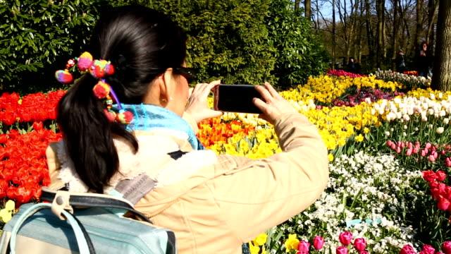 Aziatische mensen gebruikend smartphone voor nemen foto tulpen bloem Keukenhof boerderij.  Lente seizoen