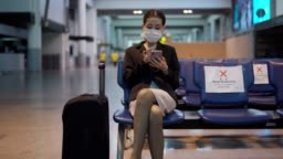 Asian people wearing a mask sitting in airport distance for one seat from other people keep distancing protect from COVID-19 virus