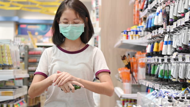 asian people wearing protect mask and spray disinfectant alcohol on hand to prevent  spreading of the coronavirus ( covid-19) - singapore stock videos & royalty-free footage