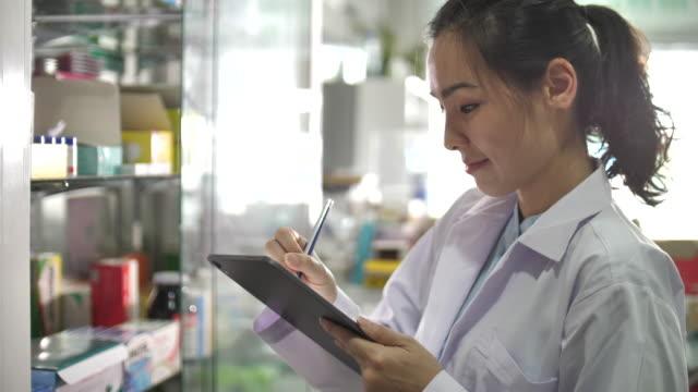 vídeos de stock e filmes b-roll de asian pharmacist using digital tablet in pharmacy - medicamento de prescrição