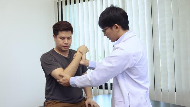 vídeos y material grabado en eventos de stock de los fisioterapeutas asiáticos comprueban los codos de los pacientes que se han sometido a rehabilitación ortopédica. - fragilidad