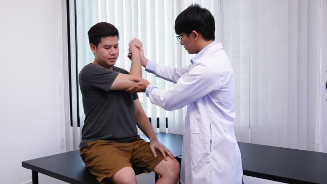 アジアの理学療法士は、整形外科リハビリテーションを受けた患者の肘をチェックします。 - マッサージする点の映像素材/bロール