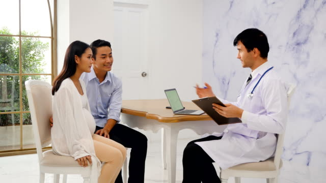 asian pregnant woman and her husband meeting with obstetrician in clinic - obstetrician stock videos and b-roll footage
