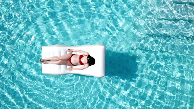 asian pregnant woman in red bikini on inflatable floats top view in pool - inflatable stock videos & royalty-free footage