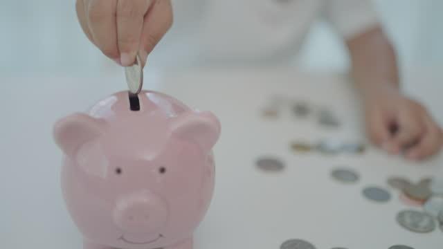 アジアの就学前の男の子は、自宅のリビングルームで彼の将来のために貯金箱にコインを入れてお金を節約します。 - home economics点の映像素材/bロール