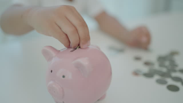 アジアの就学前の男の子は、自宅のリビングルームで彼の将来のために貯金箱にコインを入れてお金を節約します。 - 稼ぐ点の映像素材/bロール