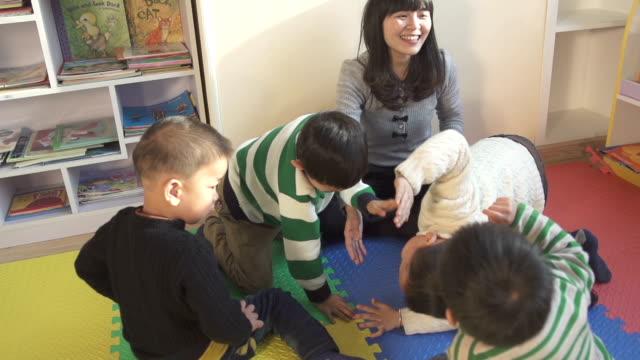 Asian preschool teacher play game with children in classroom
