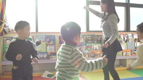 vídeos y material grabado en eventos de stock de juegos asiáticos de preescolar maestro juegue con los niños en clase, cámara lenta. - maestro