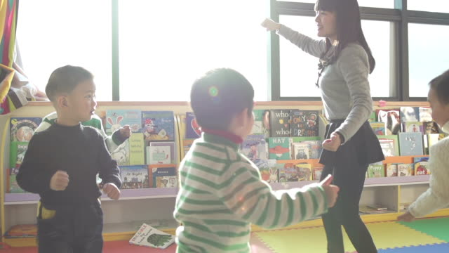 Asian preschool teacher play game with children in classroom,slow motion.