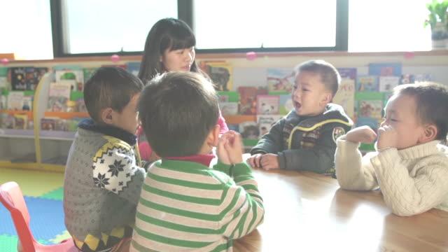 vídeos de stock e filmes b-roll de asiático professor pré-escolar ensinando crianças em sala de aula - edifício de infantário