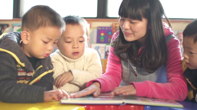stockvideo's en b-roll-footage met asian preschool teacher teaching children in classroom - peuterschool gebouw