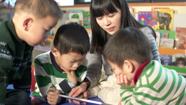 Asian preschool teacher teaching children with digital tablet