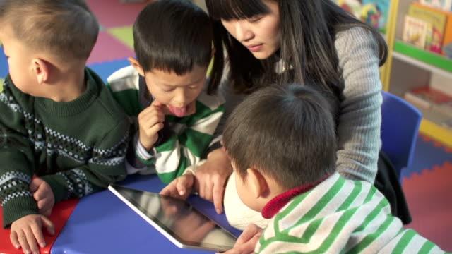 vídeos de stock e filmes b-roll de asiático professor pré-escolar ensinando crianças com tablet digital - edifício de infantário