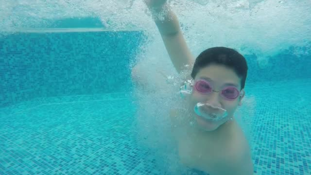 asian preteen boy jumping in pool and swimming under water. - swimming goggles stock videos & royalty-free footage