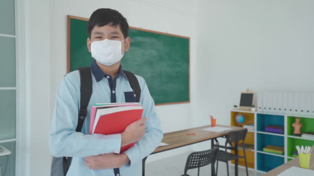 asian primary students boy with backpack and books wearing masks to prevent the outbreak of covid 19 in classroom while back to school reopen their school, new normal for education concept. - primary school child stock videos & royalty-free footage