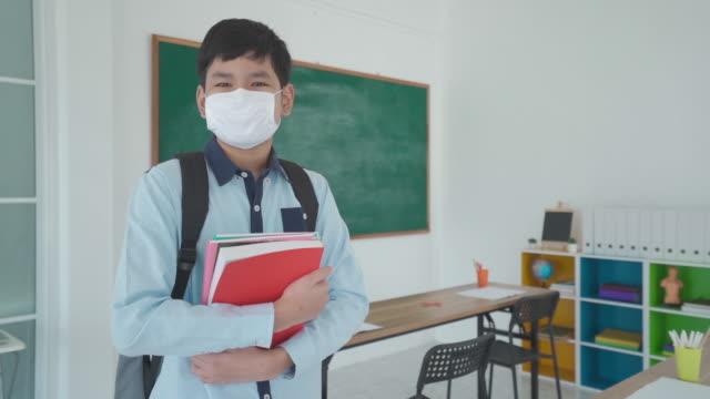 学校に戻っている間、教室でcovid 19の発生を防ぐためにバックパックとマスクを着用した本を持つアジアの小学生の少年、教育の概念のための新しい正常。 - 新学期点の映像素材/bロール