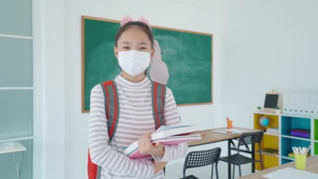 学校に戻っている間、教室でcovid 19の発生を防ぐためにマスクを着用したバックパックと本を身に着けているアジアの小学生の女の子、教育の概念のための新しい正常。 - 新学期点の映像素材/bロール