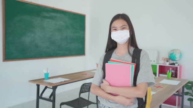 asian primary students girl with backpack and books wearing masks to prevent the outbreak of covid 19 in classroom while back to school reopen their school, new normal for education concept. - primary school child stock videos & royalty-free footage
