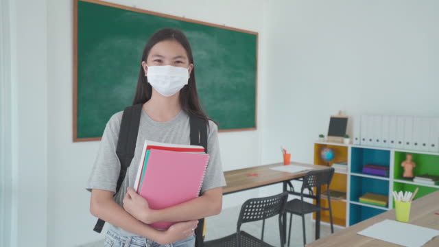 asian primary students girl with backpack and books wearing masks to prevent the outbreak of covid 19 in classroom while back to school reopen their school, new normal for education concept. - back to school stock videos & royalty-free footage