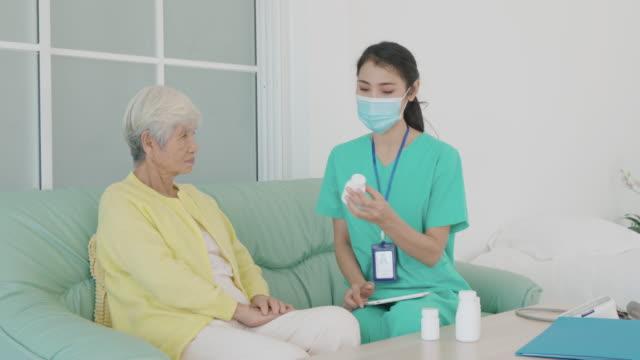 asiatische professionelle krankenschwester oder hausgesundheitshelfer, die medikamente an senior frau im wohnzimmer zu hause. ältere patienten zu hause gesundheitsversorgung und medizinisches konzept. - hausbesuch stock-videos und b-roll-filmmaterial