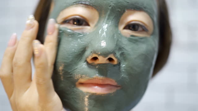 asian put on her face a green moisturizing mask - algae stock videos & royalty-free footage