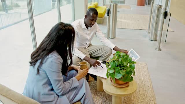 asian realtor and black businessman examining floor plan - lobby stock videos & royalty-free footage
