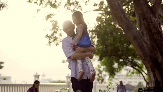 asian retire man hold his granddaughter at sunset - grandchild stock videos & royalty-free footage