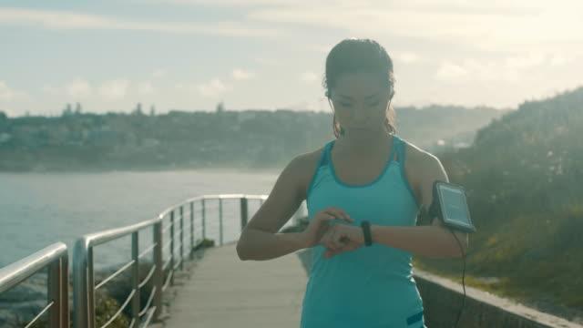 vídeos de stock, filmes e b-roll de asiático corredor ajustando o telefone inteligente (câmera lenta) - só uma mulher de idade mediana