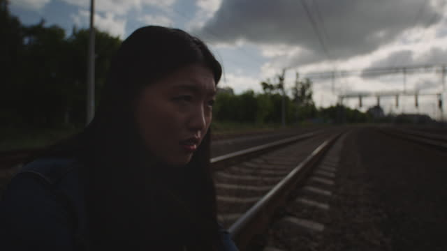 Asian sad woman sitting on the railroad truck.